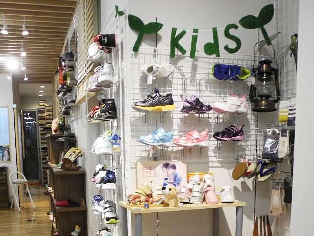 こども靴コーナー。アシックスのスクスクを中心に展示してます。子供用に小さなフィッティングチェアーも用意しています。